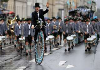 A man on a high-wheel bicycle and musicians participate in the traditional costume and riflemen parade during the Oktoberfest in Munich.