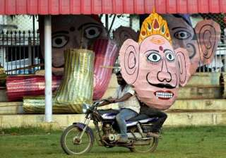 A man carrying effigy of Ravana on his bike.