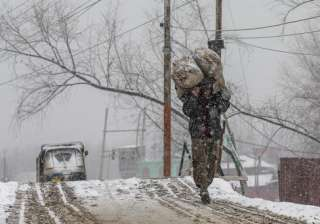 A Kashmiri Labourer carries sacks of charcoal as it snows in Srinagar.