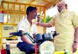 PM Narendra Modi interacts with an e-rickshaw beneficiary