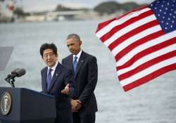 Shinzo Abe delivers remarks as Barack Obama looks during