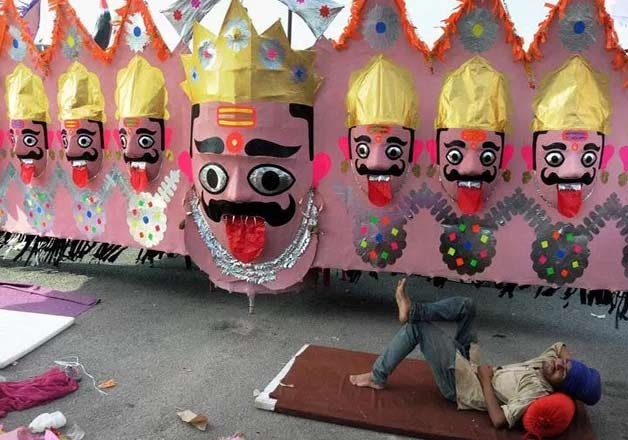 A labourer rests near an effigy of the demon king Ravana on the eve of Dussehra festival in Amritsar.
