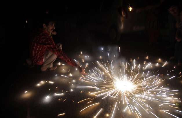 An Indian lights firecrackers to celebrate Diwali, the Hindu festival of lights, in Jammu, India. Hindus across the country are celebrating Diwali where people decorate their homes with light and burst firecrackers.