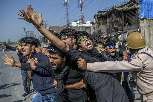 Kashmiri Shiite Muslims shouts pro-freedom slogan after they were detained for participating in a religious procession during curfew in Srinagar.