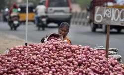 A woman arranging onions near a road in Chennai