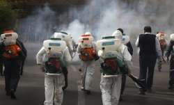 A file photo of health workers spraying disinfectants on