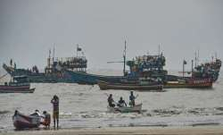 Fishing boats seen anchored at a shore following a warning