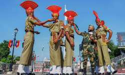 Border Security Force (BSF) soldiers offer sweets to each other during the 74th Independence Day cel
