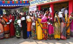 Voters show their identity cards as they stand in a queue