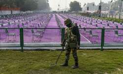 A security person inspects a lawn as preparations underway near the India Gate for the upcoming Repu