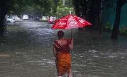 A woman walks through a flooded street during heavy rains.