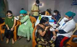 Health workers administer COVID-19 vaccine dose to