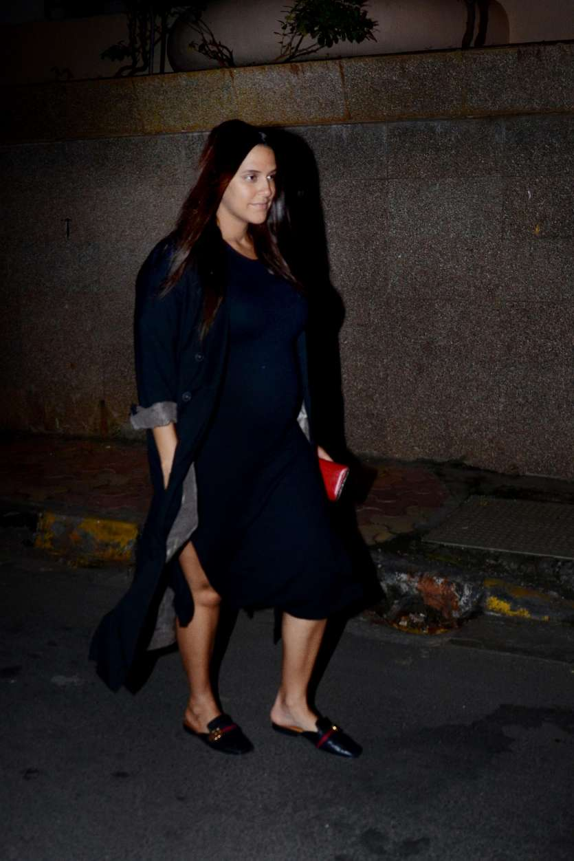 Neha looked radiant in a black dress with a black jacket, whereas Angad kept it casual in a blue tee and black track pant. The couple obliged media with photos.