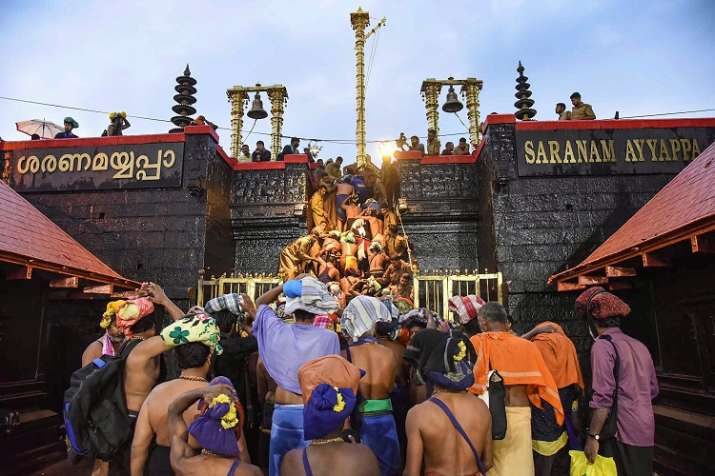 Devotees enter the Sabarimala temple as it opens amid