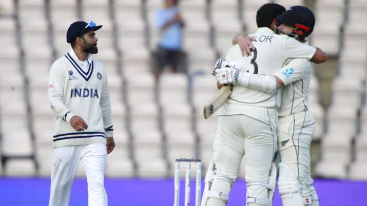 Virat Kohli, left, reacts as New Zealand's captain Kane Williamson, right, and Ross Taylor celebrate